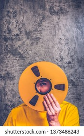man holding vintage reel footage film on grunge texture cement wall background. movie, film, video editing concept