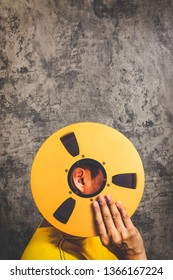 man holding vintage reel tape on grunge texture cement wall background. music, recording, movie, song concept