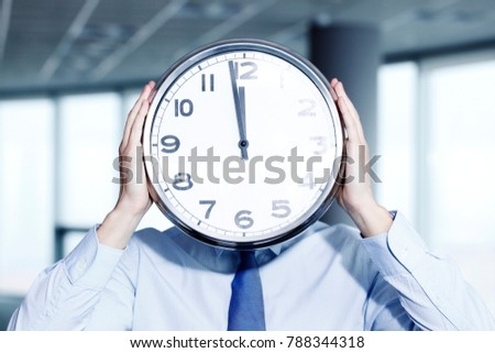 Man holding wall clock in office, deadline concept
