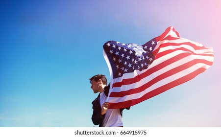 man is holding waving american USA flag.