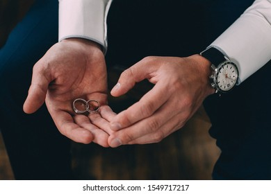 man holding wedding rings in hands