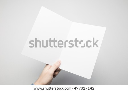 man holding white bi fold paper flyer stock photo edit now