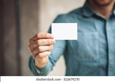 Holding business card stock images royalty free images vectors man holding white business card on concrete wall background reheart Choice Image