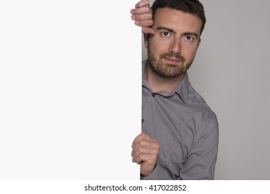 man holding a white cardboard isolated on gray background