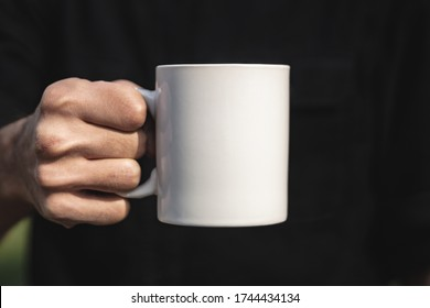 Man holding a white cup of hot beverage outdoors. Man's hand holding a blank mug against black background. Close up, mockup image, copy space for text.