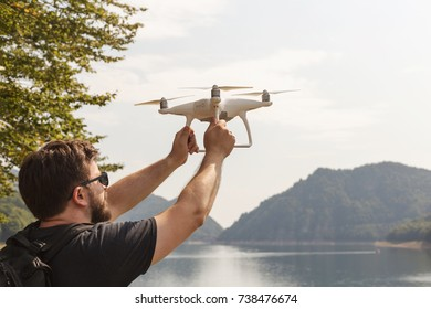 Man is holding white drone near Lake Vidraru at Fagaras Mountains. Romania
