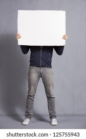 Man holding white empty signboard with space for text in front of his face, isolated on grey background.