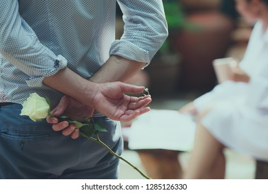 Man holding white rose and wedding ring  behind his back for making marriage proposal surprised with women.
