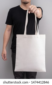Man holding a white tote bag canvas fabric on grey background