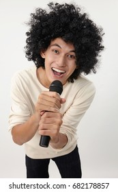 man holding a wireless microphone singing