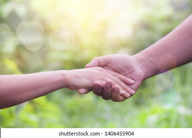 a man holding woman hand over blurred green natural background with bokeh light, Business man and woman shaking hands,helping hand and world peace concept with copy space