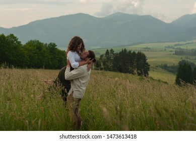 Man is holding woman in heads and girl is smailing. Happy couple on meadow with view to mountains