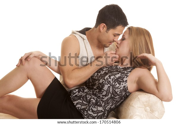A man is holding a woman's chin and is about to kiss her.