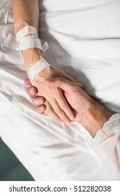 Man holding woman's hand with fall risk bracelet on wrist in hospital. Male and female hands on white bed.