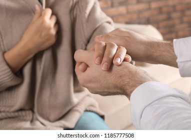 Man holding woman's hand indoors, closeup. Concept of support and help