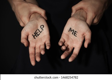 Man holding woman's hands with words HELP ME on dark background, closeup. Stop sexual assault