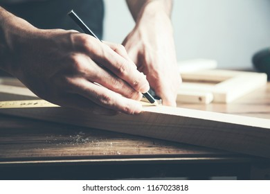Man holding wood and pencil