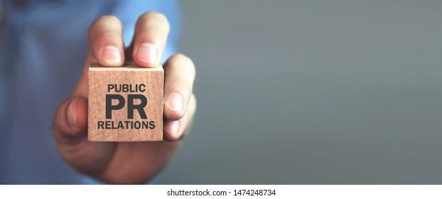 Man holding wooden cube. Pr- Public Relations