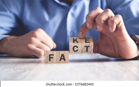 Man holding wooden cubes. Fact or fake. Business concept