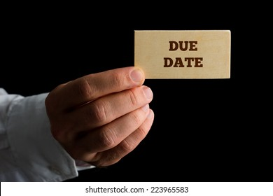 Man holding a wooden sign saying Due Date conceptual of a repayment date or final date for payment of an obligation.