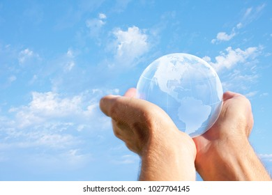 Man holding world globe in his hands against a blue sky