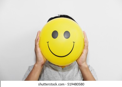 A man holding yellow balloon with smile face emotion instead of head. Positive Thinking concepts