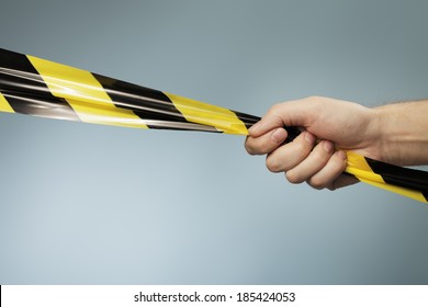 Man holding a yellow and black plastic barrier tape in his hand.