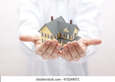 Man holding yellow house miniature