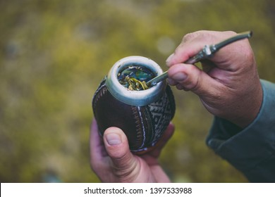 Man holding yerba mate in nature. Travel and adventure concept. Latin American drink yerba mate.