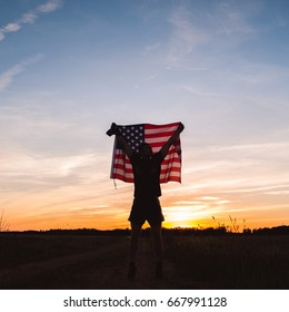 a man holds an American flag at sunset to celebrate the holiday in the countryside, the silhouette of a man
