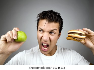 Man holds apple and burger while looking agitated