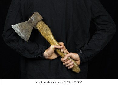 A man holds an axe behind his back on a black background