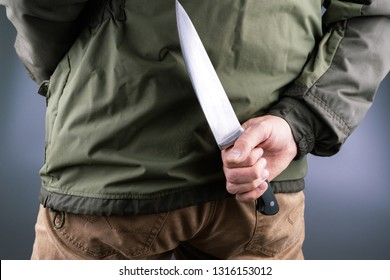 a man holds back a large chef's knife, green jacket yellow pants grey background