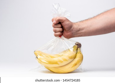 A man holds banana in a plastic bag