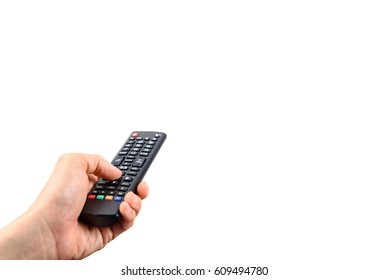 Man holds a black remote control in a left hand. A remote control is a component of an consumer electronic device used to operate the device wirelessly from a distance. Isolated on white background.