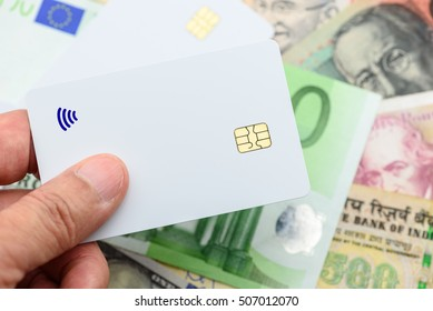 Man holds a blank white surface hybrid or smart card with a chip and a contactless signal logo. Preparing to pay a digital / virtual money instead of physical money or banknotes in a retail shop.