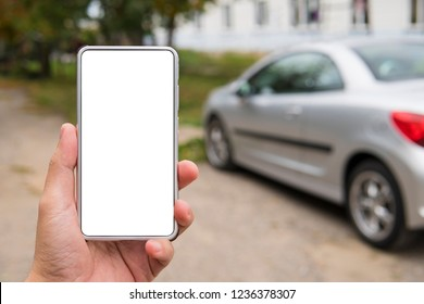 Man holds a blank-sreen smartphone in the left hand near the parked vehicle. Person in the street uses car link application on cell phone. Remote engine start by using phone app. Trip computer start.