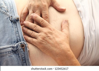 a man holds both hands to his abdominal area