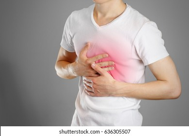 A man holds the Breasts. The pain in his chest. Heartburn. Stomach hurts. Sore point highlighted in red. Closeup. Isolated.