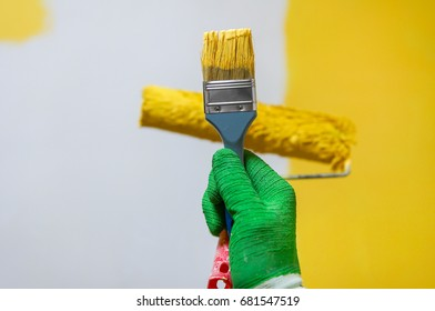 Man holds brush and roller brush with yellow paint over yellow half painted wall