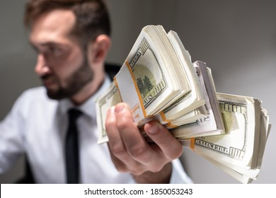 Man holds bundles of money in his hands. Several packs of dollars in hands of a businessman. Businessman demonstrates his income. Man holds out dollars to screen. Blurred background.