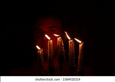A man holds a burning candle in a candlestick and illuminates his path. A man in a dark room, burning candles illuminate his face. Candles are burning in a dark room. Selective focus.