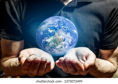 The man holds carefully in his hands the glowing planet earth