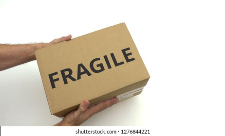 Man holds carton with FRAGILE text