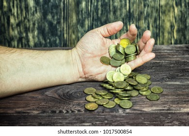 A man holds a coin in his hand.