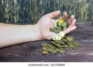 A man holds coins in his hand.