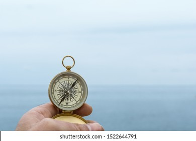 Man holds a compass against the horizon of the sea one day with fog