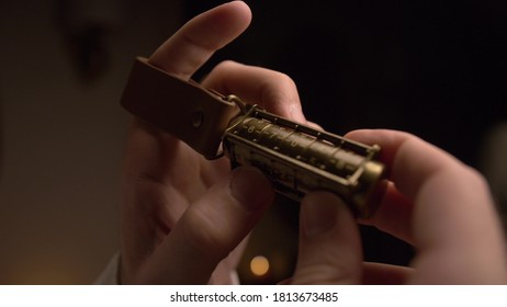 A man holds a copper cryptex with numbers. He calculates the cryptex code with his hand. At the end of the cryptex, a leather strap is put on the man's finger. There is a dim light in room. Closeup.