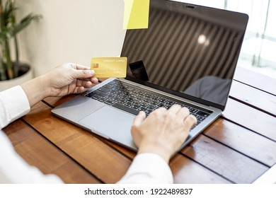 A man holds a credit card and uses a laptop. He is filling out credit card information for online shopping, credit cards can be used to pay for goods and services through physical stores and online.