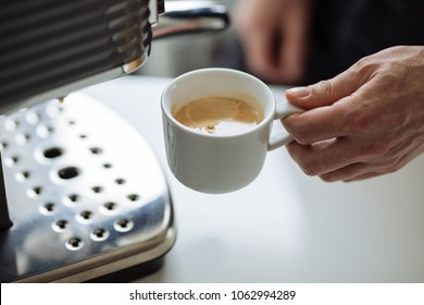 The man holds cup of espresso next to a coffee maker